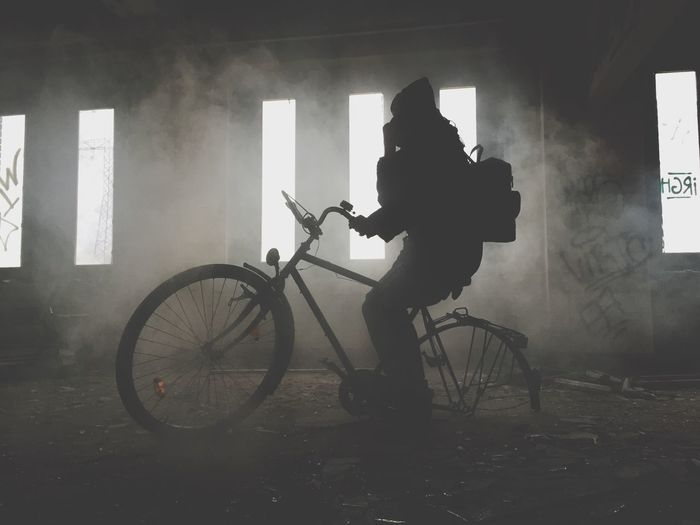 Silhouette person on bicycle in abandoned house