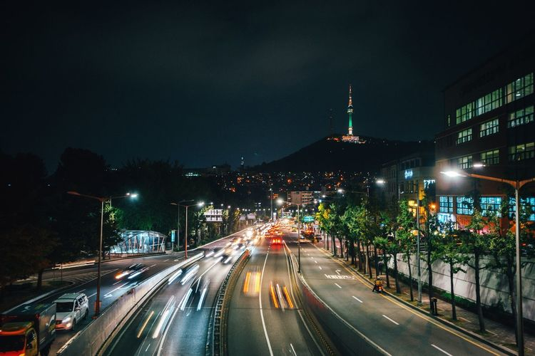 Distant View Of N Seoul Tower With City Street In Foreground At Night