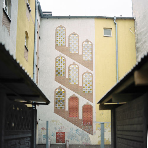 An unusual pattern of bricks and glass decorate the exterior of an apartment complex in Poznań, Poland. Apartment Buildings Flats Interesting Poland Polska Poznań Quirky Stairs Travel Apartments Architecture Art Artworks Building Exterior Built Structure Creative Day Grey House No People Outdoors Overcast Pattern Polish Window