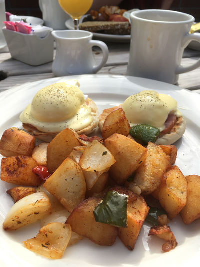 Al fresco brunch of eggs Benedict and home fries potatoes. Two poached eggs, potatoes and coffee on white dinnerware for an outdoor Sunday brunch in Brooklyn. Breakfast Breakfast Breakfast Time Breakfast ♥ BreakfastTime  Brunch Brunch Breakfeast Brunch Of The Day Brunch Time Brunch 😊 Brunching Brunchtime Close-up Coffee Day Eggs Benedict Eggs Benedict Breakfast Eggs Benedict On English Muffin, White Plate On Slate Background Food Food And Drink Food And Drink No People Plate Sunday Brunch Table