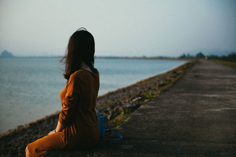 Side view of woman looking at sea while sitting on retaining wall against sky during sunset