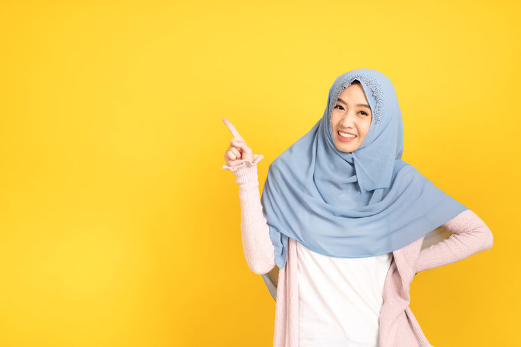 Young woman standing against yellow background