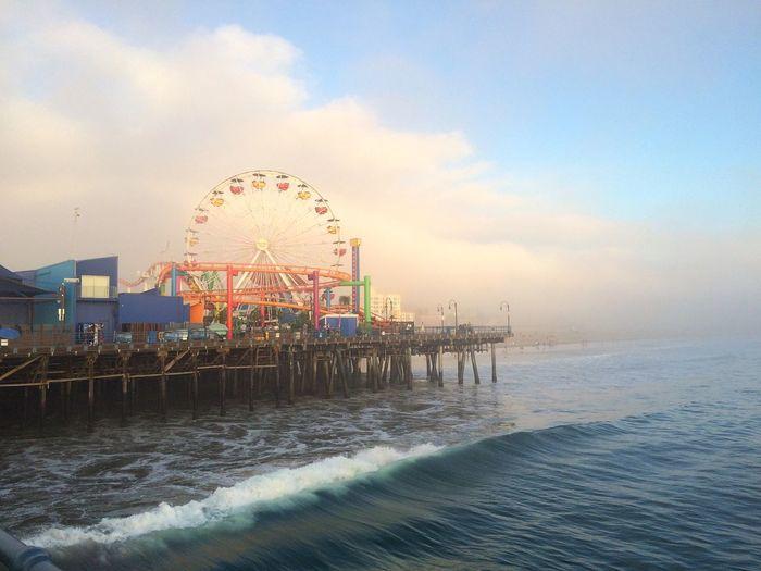 Ferris Wheel On Santa Monica Pier By Sea Against Cloudy Sky