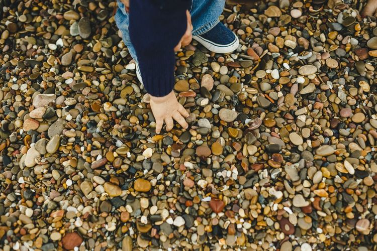 Low section of boy standing on pebbles
