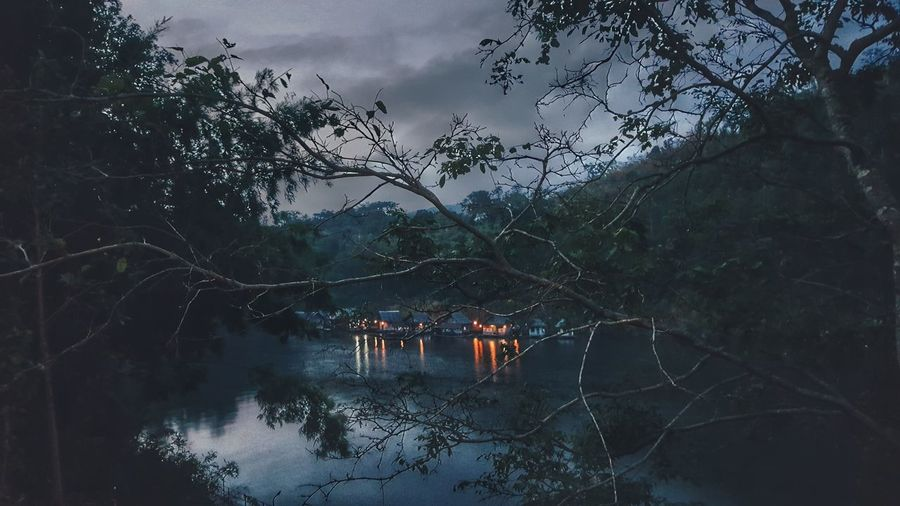 Small Fairy Village on the River at Dawn. Tree Water Nature Sky Mountain Cloud Storm Night Light Town House Quiet Kanchanaburi Thailand