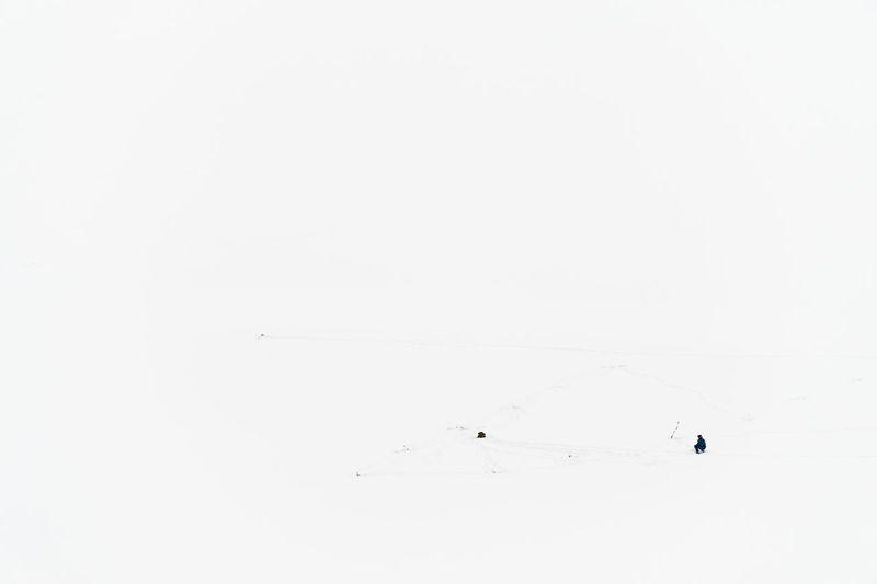 Lonely ice fisherman with hand auger on the frozen Volga River photographed from above. Foot tracks barely visible in the snow covering the ice and a backpack / rucksack. Copy Space White Color White Background Backgrounds Full Frame Winter Cold Temperature Tranquility Frozen River Volga River Ice Fishing Solitude Solitary Russia Auger Winter Sport Relax Free Time