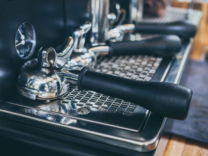 Portafilter upside down on coffee machine on wooden table in cafe. Indoors  Close-up Metal No People Table Machinery Technology Selective Focus Retro Styled Still Life Connection High Angle View Focus On Foreground Equipment Black Color Day Coffee Shop Food And Drink Silver Colored Portafilter Barista Coffee Cafe Tool Machine