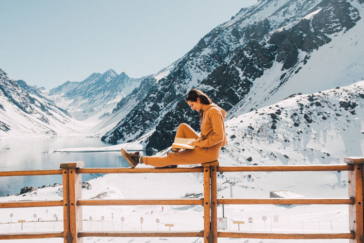 Woman sitting on snow covered mountain