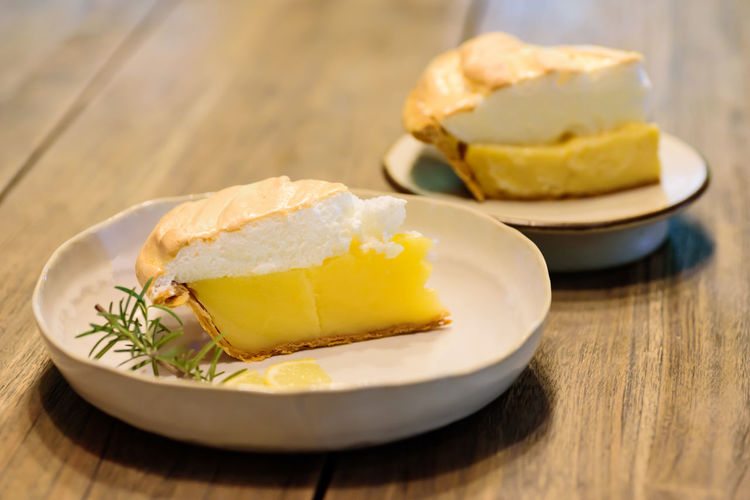 Piece of lemon meringue pie on white dish Bakery Cake Citrus  Close Up Cream Cuisine Culinary Delicious Dessert Dish Eating Food Fresh Gourmet Juicy Lemon Meringue Pie Piece Sweet Table Tart Tasty Wood Wooden Yellow Food And Drink Ready-to-eat Serving Size SLICE