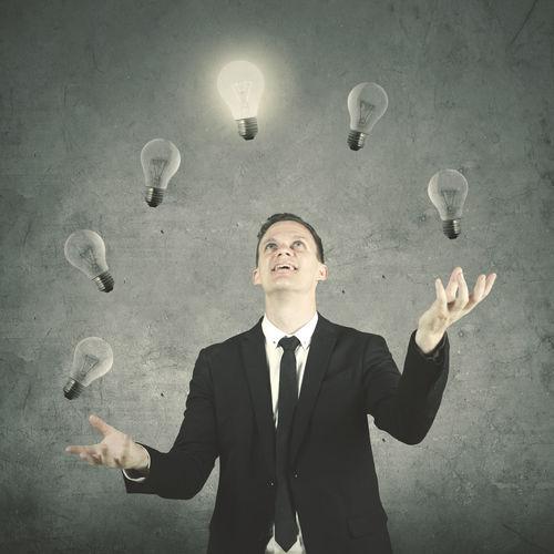 Digital composite image of businessman juggling light bulbs against wall