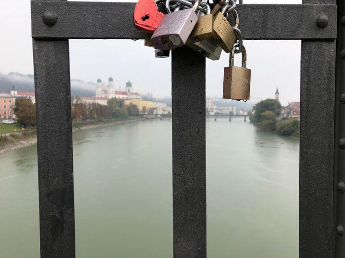 Close-up of padlocks hanging on bridge over river