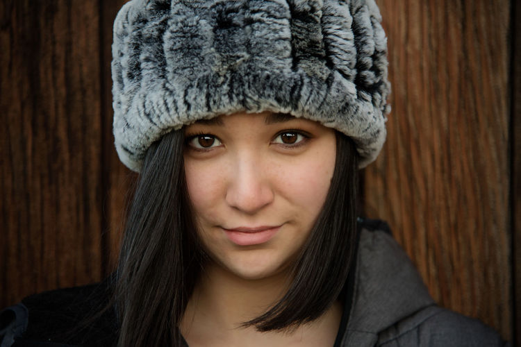 Close-up portrait of teenage girl wearing hat against wall