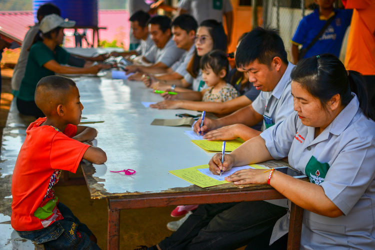 Chiang Rai, Thailand Volunteer Medical Healthcare And Medicine Public Dental Hospital Thailand Help Child Childhood Boys Men Group Of People Males  Real People Table Girls Women Sitting Females Offspring People Education Togetherness Classroom School Innocence