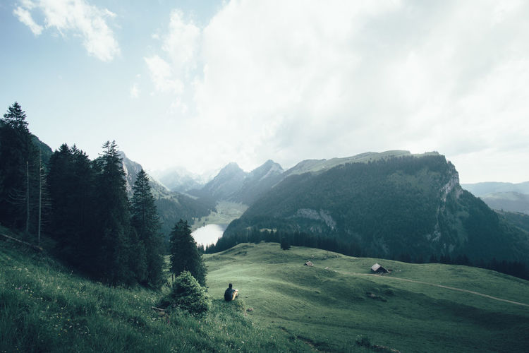 Man sitting on grassy hill against alps