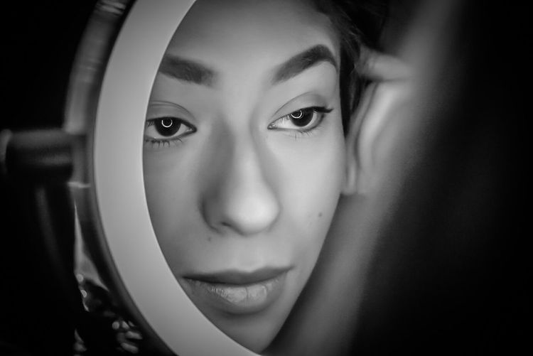 Close-up of young woman reflecting in mirror