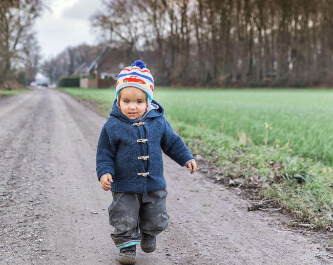 Happy toddler running on footpath – Kempen, Germany Adventure Baby Babyhood Babygirl Boots Building Exterior House Caucasian Cheerful Coat Duffle Coat Curiosity Dirty Messy Muddy Exploring Field First Steps Footpath Germany Girl Girls Females Happiness Happy Hiking Hikingadventures Hurry Jacket Joy Lonely Looking Away Motion Speed on the move Pants Portrait People Running Jogging Rural Scene Smiling Smile Solitude Toddler  Toddlerlife Wanderlust Walking Healthy Lifestyle Winter Child Childhood One Person Men Males  Clothing Full Length Casual Clothing Front View Day Nature Innocence Shoe Road Cute Boys Hat Focus On Foreground Warm Clothing Outdoors Rubber Boot Jeans