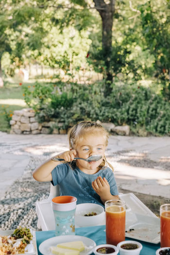 Girl eating food while sitting outdoors