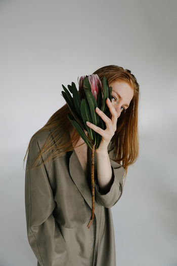 Studio Shot Indoors  Front View Young Adult Young Women Hairstyle Hair Obscured Face Flowering Plant Protea Plant Girl Fashion Fashion Model Fashion Photography Girls Women Woman Beautiful Beautiful Woman Gray Background Holding Flower Waist Up Standing Leisure Activity Lifestyles One Person Casual Clothing Hiding Gingerhair Redhead Style