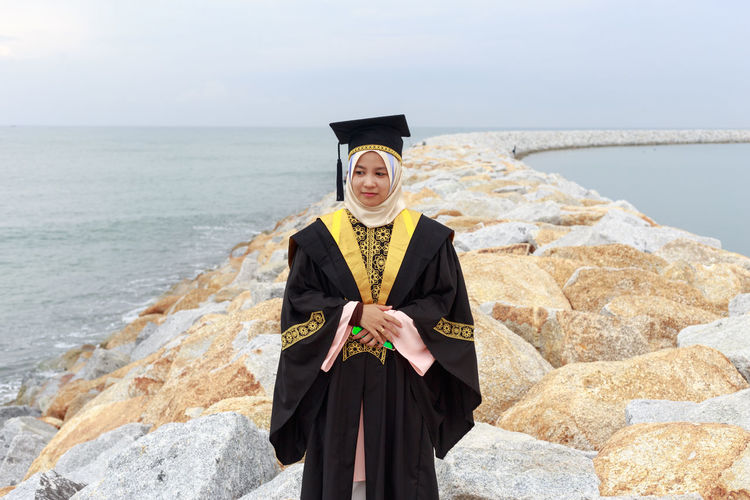 Young woman wearing graduation gown on groyne at sea