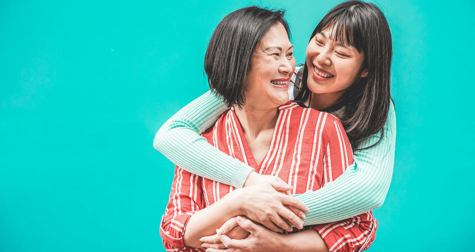 Smiling daughter embracing mother against turquoise background