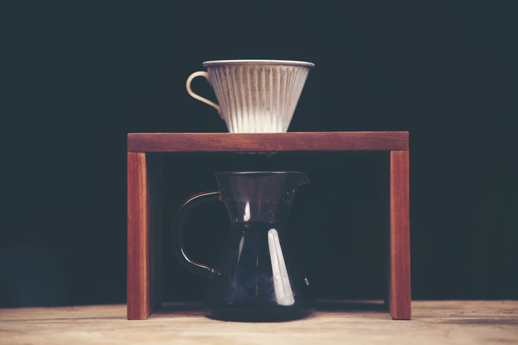 Close-Up Of Black Coffee In Jar On Table Against Black Background