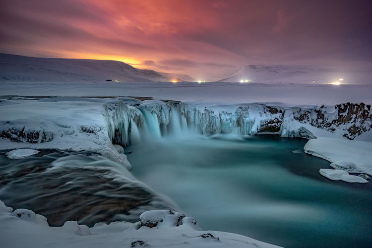 Scenic view godafoss falls on snowcapped mountains against sky during sunset