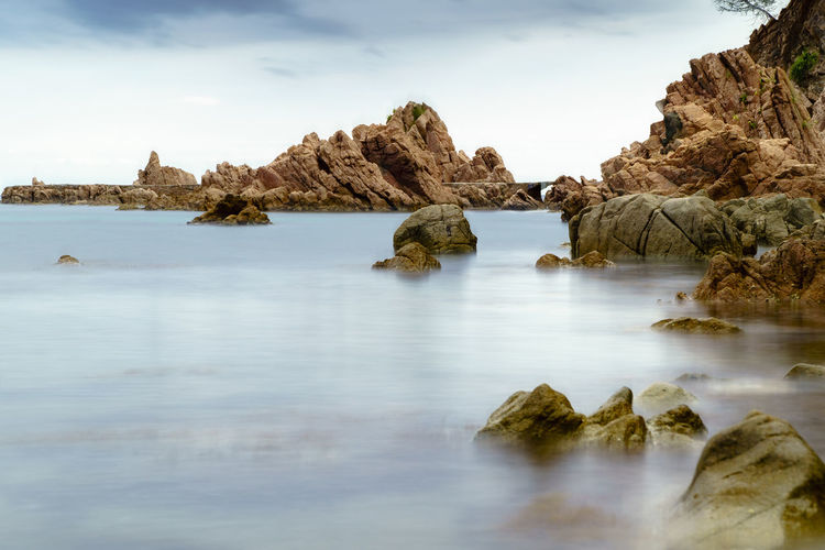 Rocks in sea against sky