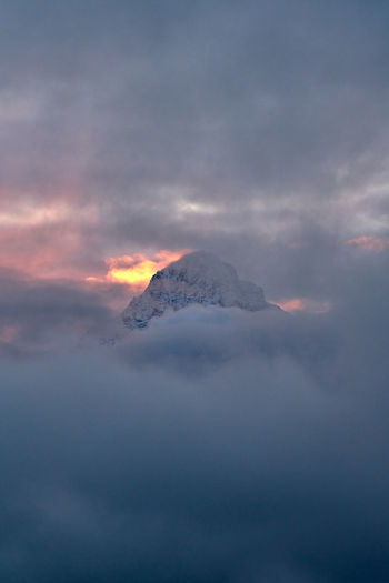 Scenic view of snowcapped mountain amidst clouds