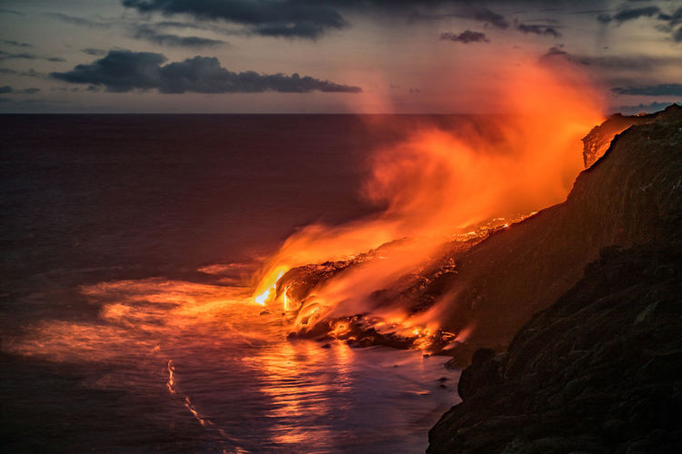 As the hot lava reaches the cold waters of the Pacific ocean, the wind mixes the steam with the hot air over the molten rock. The result is spectacular. Especially at night, when the toxic gasses are illuminated by the orange light. This is the hot breath of Pele, the goddess of the volcano. Atmosphere Beauty In Nature Big Island Coastline Dramatic Sky Environment Evening Fire Hawaii Horizon Over Water Idyllic Kalapana Landscape Lava Majestic Night Non-urban Scene My Year My View Scenics Spectacular Sunset Tourism Travel Destinations Volcano Overnight Success The Great Outdoors - 2017 EyeEm Awards
