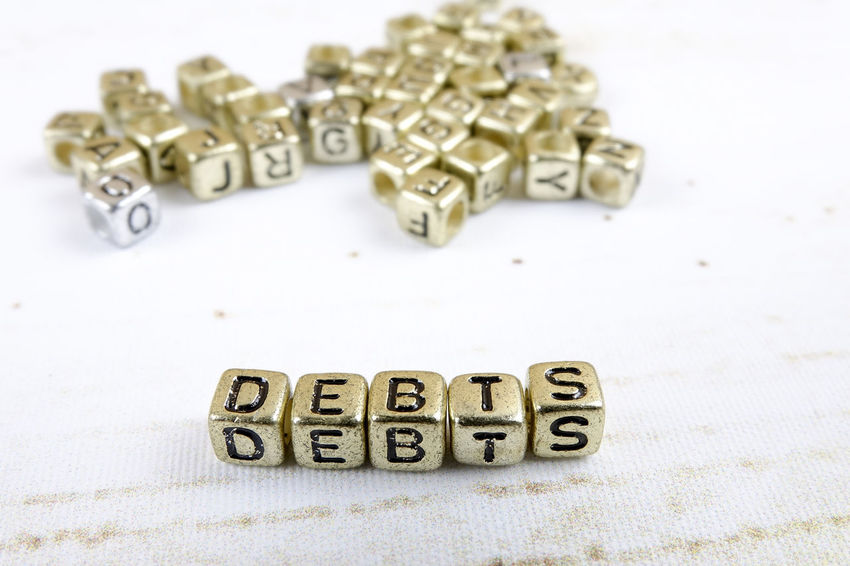 DEBT CONCEPT WITH GOLD DICE ON A WOODEN TABLE Alphabet Capital Letter Close-up Communication Credit Card Debt Crisis Focus On Foreground High Angle View Indoors  Large Group Of Objects Letter No People Number Paper Selective Focus Still Life Studio Shot Table Text Toy Western Script White Background