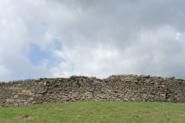 Low angle view of stone wall on field against sky