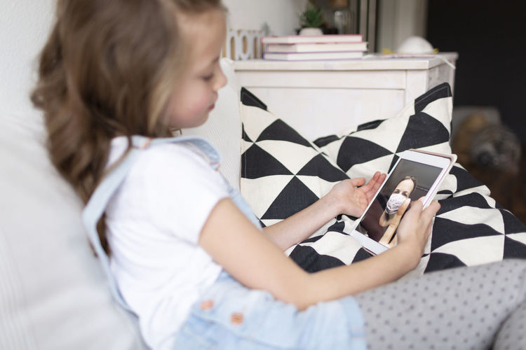 Side view of cute girl using digital tablet sitting at home
