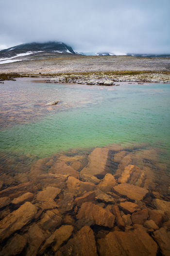 Clear mountain lake. Snøhetta hidden behind fog. Beauty In Nature Water Scenics - Nature Tranquil Scene Tranquility Cloud - Sky Nature No People Non-urban Scene Idyllic Outdoors Lake Mountain Hiking Adventures Snøhetta Norway Scandinavia Nordic Dovre Dovrefjell Moody Moody Weather Moody Nature