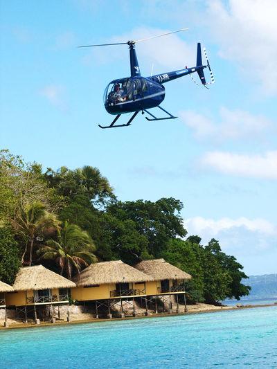 Helicopter Transfer Iririki Resort Port Vila Vanuatu . Cloud Day Flying Helicopter Iririki Mid-air Mode Of Transport Outdoors Resort Hotel Scenics Sea Sky Tour Tranquil Scene Tranquility Transfer Transportation Tree Vanuatu Vivid International Water Waterfront
