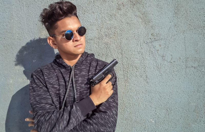 Young man wearing sunglasses standing against wall