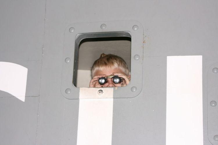 Boy looking through binoculars from window
