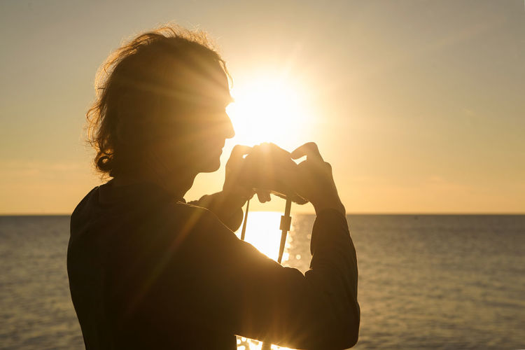 Silhouette man photographing sea against clear sky during sunset