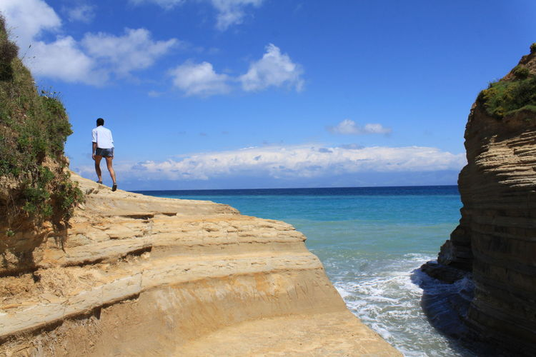 Man standing on cliff next to sea