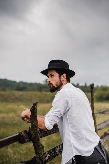 A young handsome man is standing on the green grass in the field and leans his hands on the babor. He is dressed in a white shirt and black trousers with suspenders, a hat on his head. He has hair on his face, he wears a beard. Pensive expressive look. In the background is a gray cloudy sky and a spacious meadow. Classic Fashion Field Grass Hat Masculinity Beard Casual Clothing Clothing Contemplation Facial Hair Focus On Foreground Hat Lifestyles Nature One Person Outdoors Railing Real People Side View Sky Standing Three Quarter Length Young Adult Young Men Summer Road Tripping The Portraitist - 2018 EyeEm Awards The Still Life Photographer - 2018 EyeEm Awards The Traveler - 2018 EyeEm Awards The Fashion Photographer - 2018 EyeEm Awards The Photojournalist - 2018 EyeEm Awards The Great Outdoors - 2018 EyeEm Awards The Great Outdoors - 2018 EyeEm Awards The Street Photographer - 2018 EyeEm Awards Love Is Love