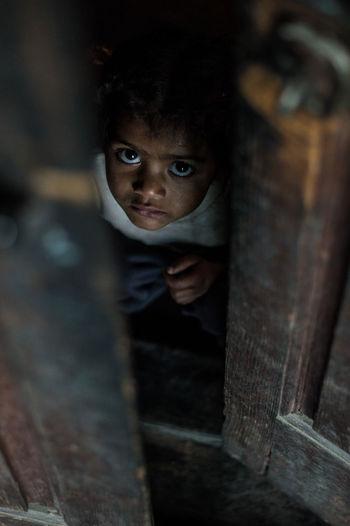 Portrait of cute boy looking through ajar door