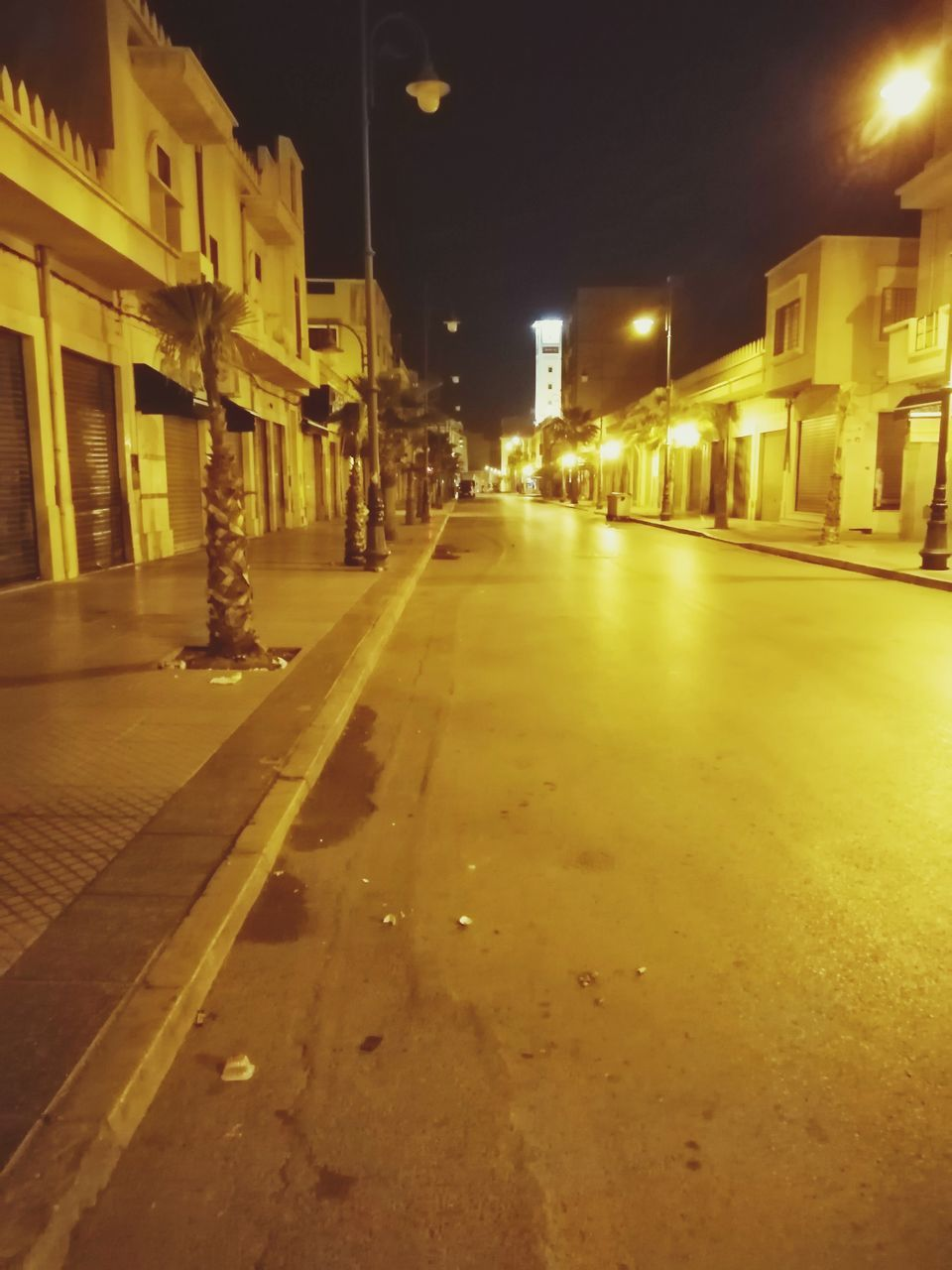 illuminated, architecture, street, night, built structure, city, building exterior, road, transportation, street light, the way forward, direction, lighting equipment, no people, building, city street, residential district, mode of transportation, car, motor vehicle, outdoors, light, surface level
