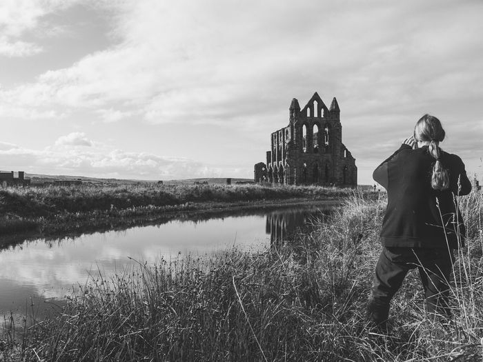 Rear view of woman standing on grassy field with whitby abbey in background