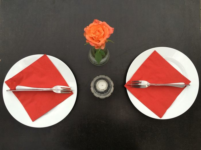 High angle view of plates with rose vase on table