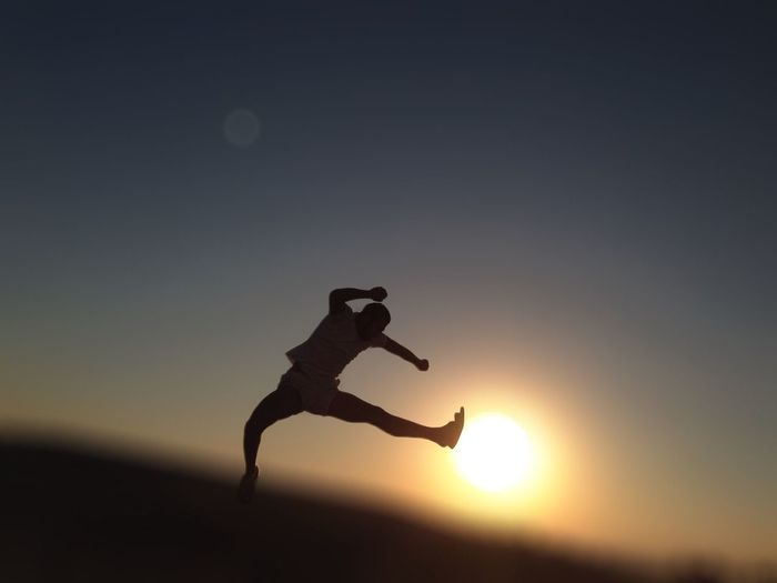 Silhouette man jumping at sunset