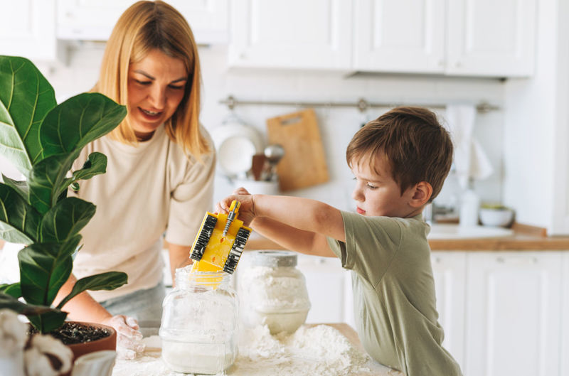 Young woman mother and her toddler boy son have fun while cooking with flour at table in kitchen