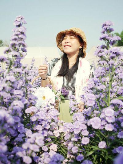 Woman standing by purple flowering plants