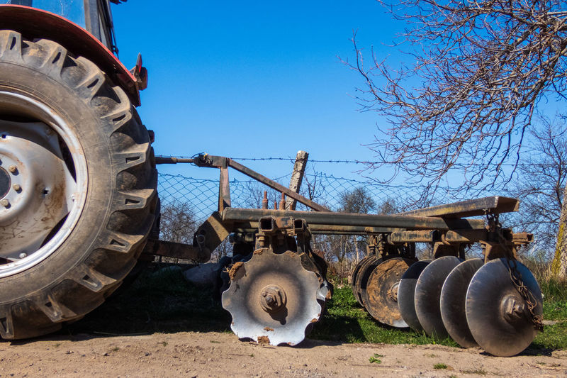 Close-up of machinery on field against clear blue sky