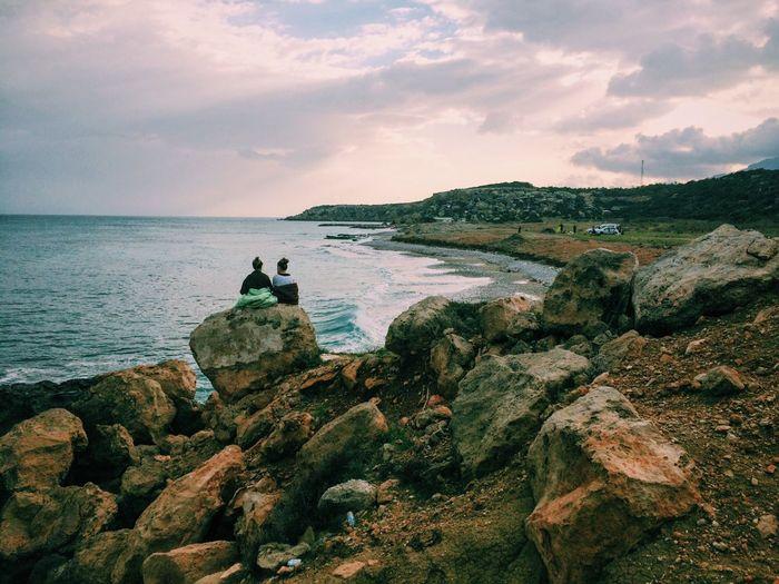 Rear View Of Women Sitting On Rocks Against Sky