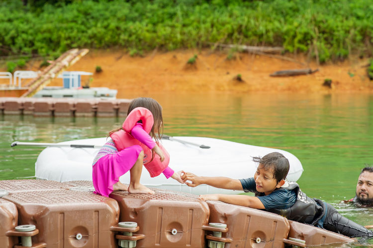 Girl holding boy hand on raft with father in lake