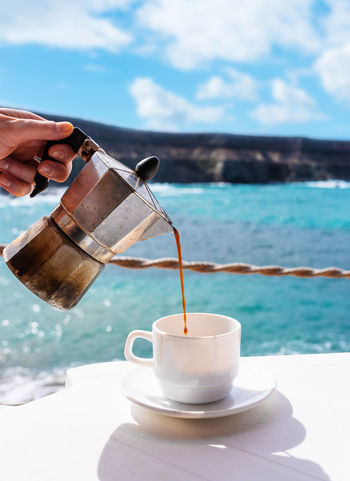 Moka Pot Caffetteria Close-up Coffee - Drink Coffee Cup Day Drink Food Food And Drink Freshness Holding Human Body Part Human Hand Italian Coffee Maker Nature One Person Outdoors People Pouring Real People Refreshment Sea Sky Sunlight Water